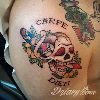 """Popularne grafiki z symbolicznym hasłem """"Carpe Diem"""" - tatuaże o niebanalnej różnorodności czcionek. """"Carpe Diem"""" na skórze nie musi ograniczać się wyłącznie do standardowej kursywy; intrygować może też hasło w innych formach."""