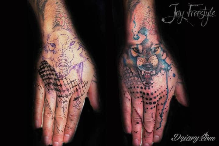 Abstrakcyjny tatuaż z wilkiem na dłoni.