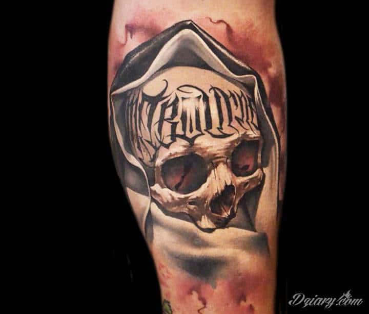Czaszka z tatuażem na czole pokryta kapturem.