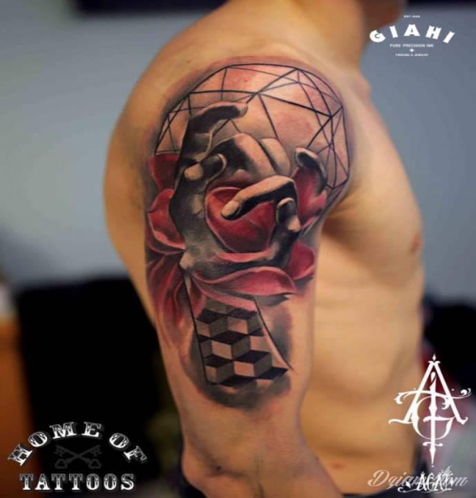 Kwiaty i geometryczne wzory z dłonią wytatuowane na ramieniu.