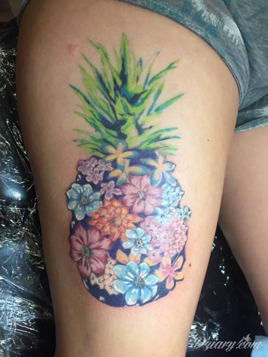 Tatuaż ananasu z kwiatów na nodze.