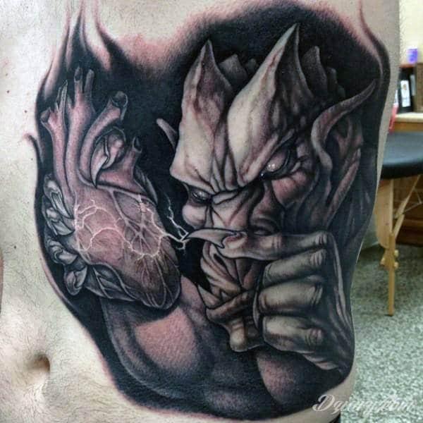 Tatuaż gargulca przebijającego serce swoim pazurem.