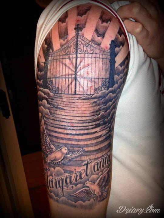 Tatuaż na ramieniu. Idąc w dół ręki: brama, schody, chmury, dwa białe gołębie i napis.