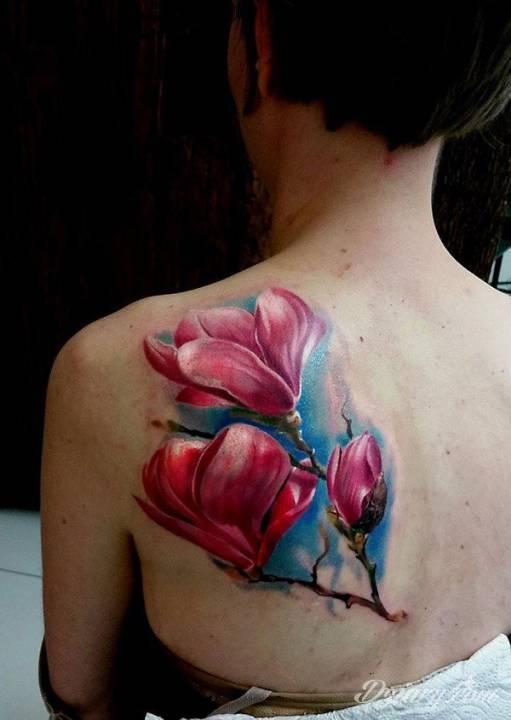 Tatuaż różowych kwiatów na łopatce.