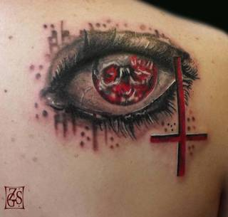 Abstrakcyjny tatuaż składający się z krzyżu, oka i czaszki.