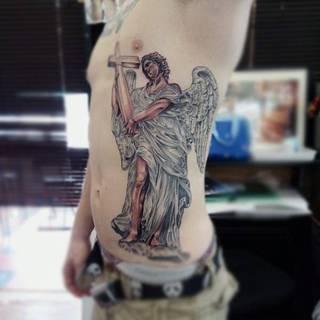Anioł z krzyżem na całym boku.