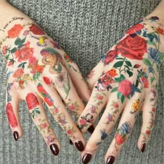 Bardzo kolorowe tatuaże na dłoniach. Duża ilość czerwieni i kwiatów. Bardzo efektowna całość