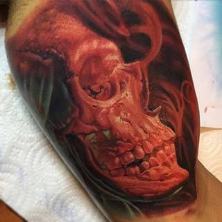 Czerwona czaszka wytatuowana na bicepsie.