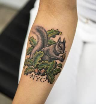 Dziara wiewiórki z orzechem na ramieniu.