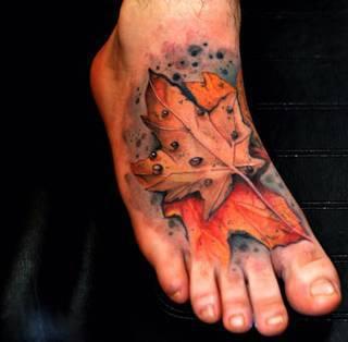 Jesienny liść wydziarany na stopie.