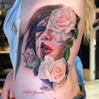 Kobieta z kwiatami wytatuowane na boku.