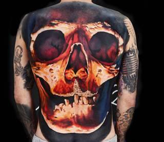 Kolorowy tatuaż czaszki na całe plecy.