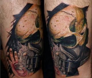 Makabryczny tatuaż czaszki w masce gazowej i ręki, z której wyrastają usta.