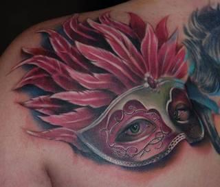 Maska z oczami kobiety wytatuowana na łopatce.