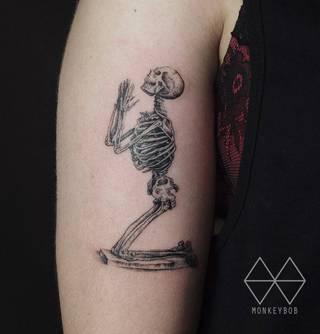Modlący się szkielet na męskiej ręce.