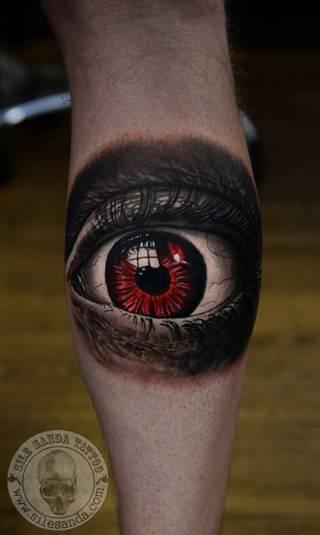 Oko z czerwoną tęczówką na nodze.