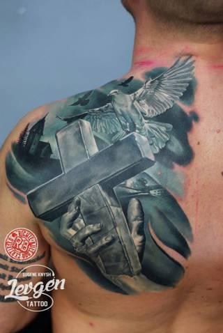 Patki i krzyż wytatuowane na plecach.