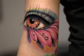 Przepiękny tatuaż: oko i kwiat. Malutkie łzy opadające na płatki. Niesamowite wykonanie. źródło: trueartists.com