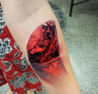 Rzucający cień rubin wytatuowany na ręce.