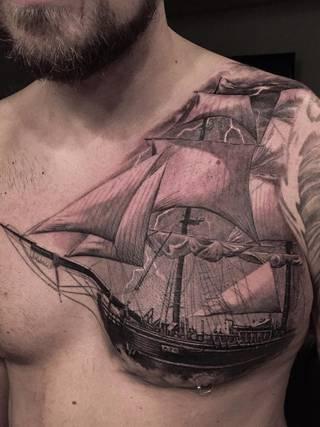 Statek na burzliwym morzu wytatuowany na lewej piersi.