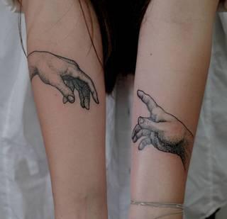 Stykające się dłonie Boga i Adama odwzorowane na przedramionach u dziewczyny.
