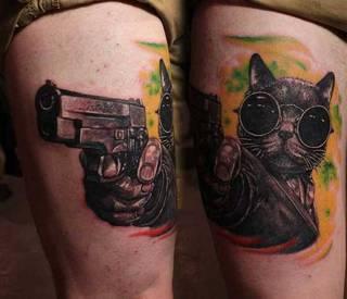 Tatuaż kota w okularach celującego z pistoletu.