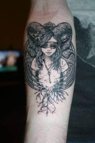 Tatuaż symbolu z oślepioną, rogatą dziewczynką na tle runicznego kręgu na przedramieniu.