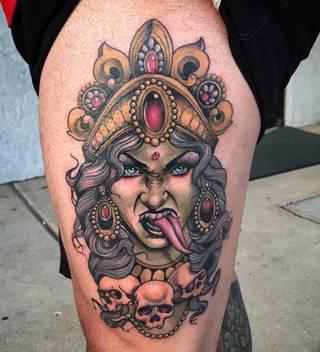 Twarz Kali wraz z czaszkami na udzie.