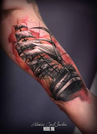 Wizerunek statku gnającego przez wody na lewym bicepsie.