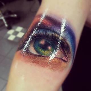 Zielone oko wytatuowane na ręce.