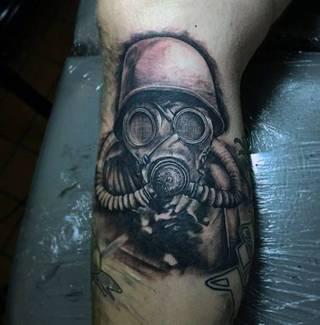 Żołnierz w masce gazowej wytatuowany na nodze.